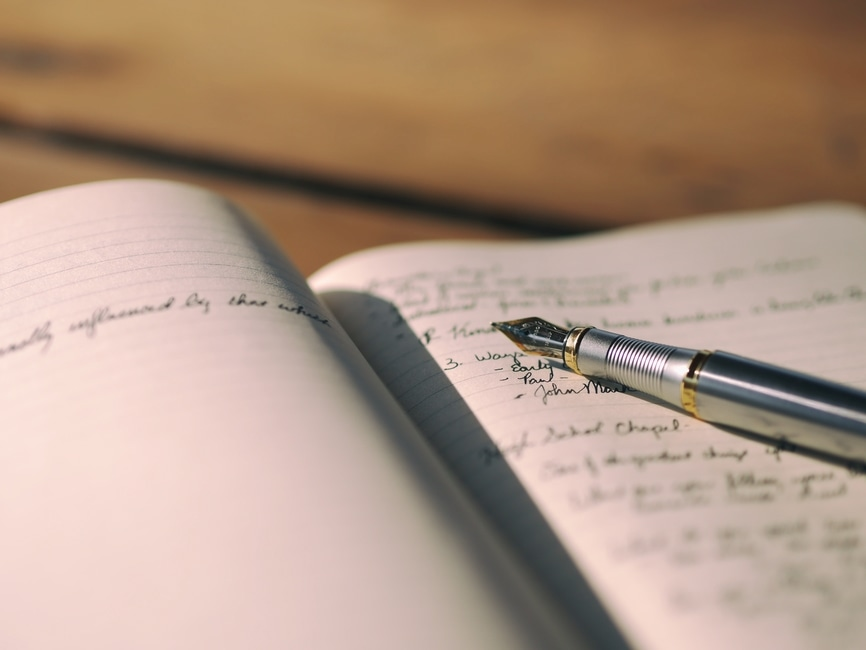 Writing in a notebook. Stock photo.