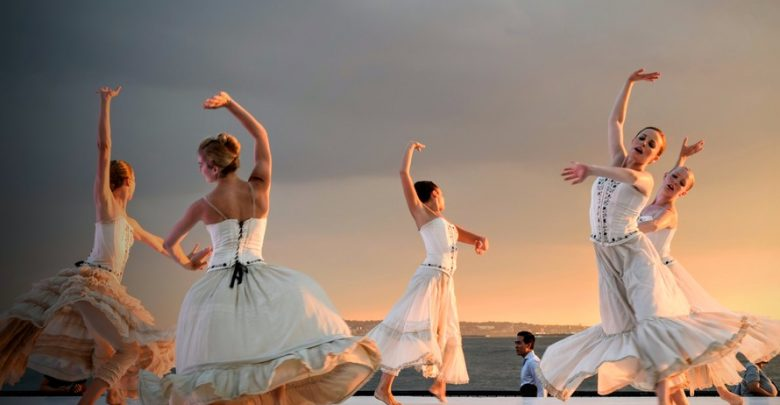 5 women pictured dancing against a sunset. Stock photo.